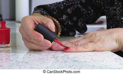 Woman keeping hand on table and apply nail polish
