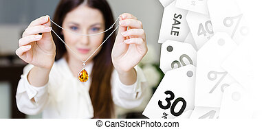 Woman keeping necklace with yellow sapphire, sale of jewelery
