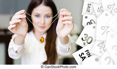 Woman keeping necklace with yellow sapphire. Special offer