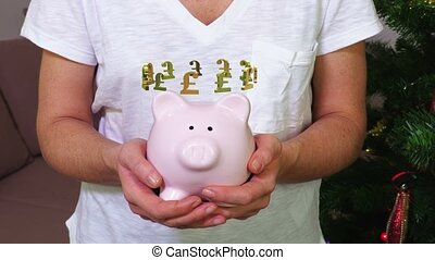 Woman keeping pink piggy bank with British pound sign concept