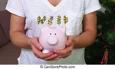 Woman keeping pink piggy bank with dollar sign concept