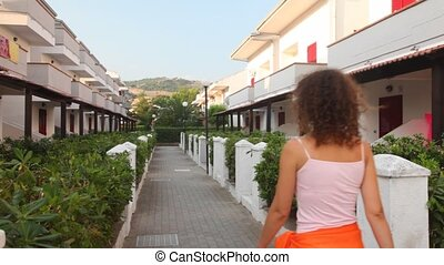 brunette woman keeps away on path between line of cottages