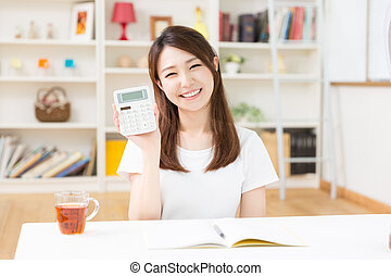 young attractive asian woman keeps household account.