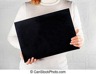 Woman keeps in hands a black empty chalkboard