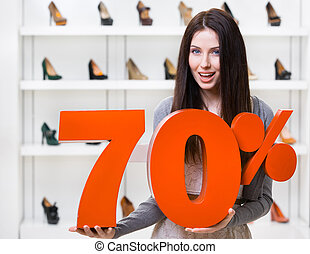 Woman keeps the model of 70% sale on pumps standing at the...
