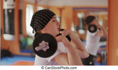 Woman kickboxer is training in a sports studio with barbell...
