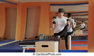 Woman kickboxer is training in a sports studio with...