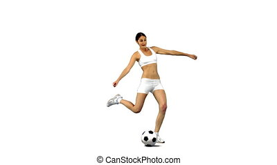 Woman kicking football in slow motion