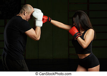 Woman kicking man in boxing fight on gym background....