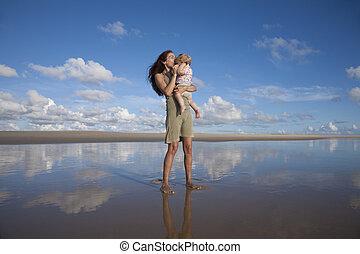 woman kisses baby at reflect beach