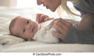 Woman  kissing a baby who is lying on a bed