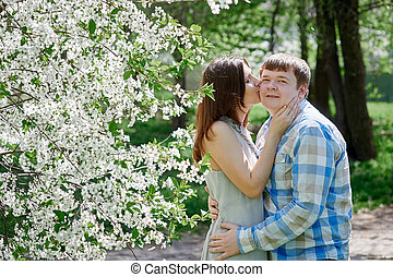 woman kissing a man in the blossoming spring garden