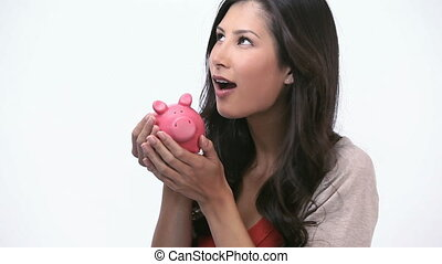 Woman kissing a piggy bank - Video of a woman kissing a...