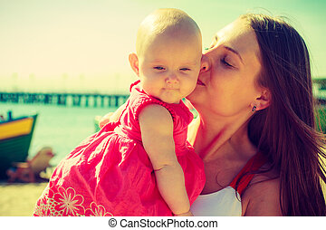 Woman kissing baby on beach near water