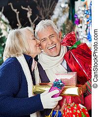 Woman Kissing Happy Man With Christmas Presents
