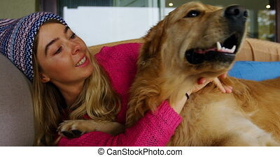 Woman kissing her dog on sofa at home 4k - Young woman...