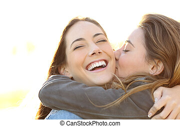 Woman kissing her happy friend with perfect smile