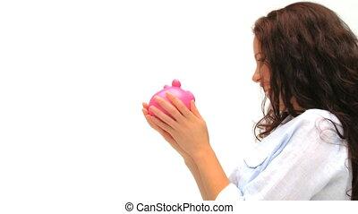 Woman kissing her piggy bank
