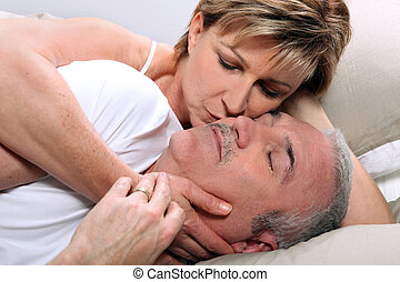 Woman kissing her sleeping husband