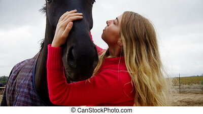 Woman kissing horse in ranch 4k - Young woman kissing horse...