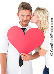Woman kissing man as he holds heart - Young woman kissing...