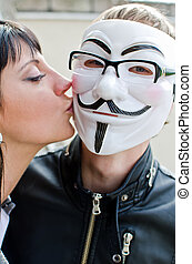 Woman kissing man in vendetta mask in glasses.