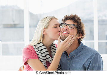 Woman kissing man on his cheek