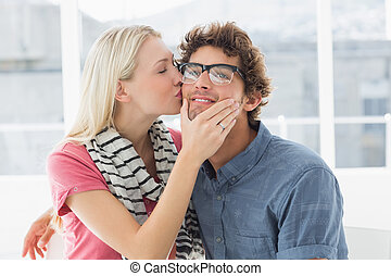 Woman kissing man on his cheek