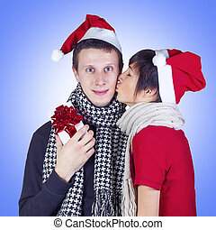 Woman kissing man with gift box
