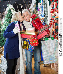 Woman Kissing Man With Stacked Christmas Presents