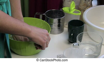 Woman kneads dough in a basin. Utensils and tools for baking bread. Cooking bread at home.