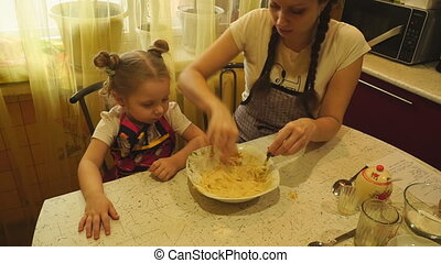 Woman kneads the dough into the plate