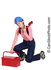 Woman kneeling by tool box
