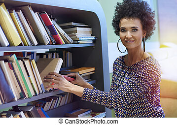 Woman kneeling next to the bookshelf
