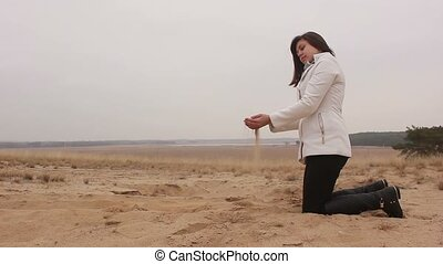 woman kneels and throws sand autumn cold nature