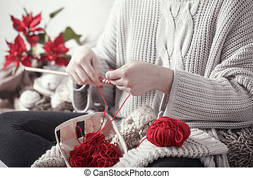 woman knits knitting needles on the couch