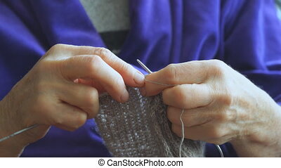 Woman knits sweater knitting needles