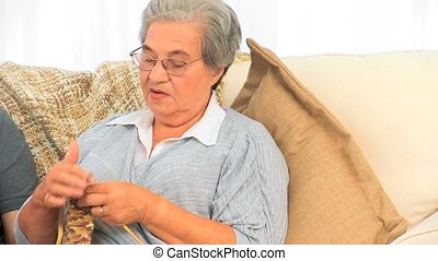 Woman knitting and talking with her