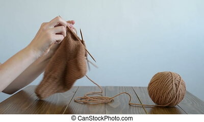 Woman knitting at a wooden table