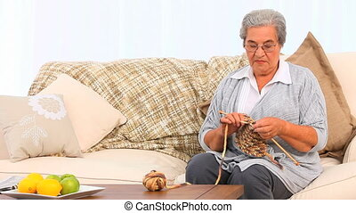 Woman knitting on her sofa