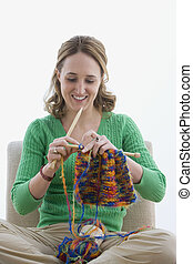 A young woman is smiling as she knits with yarn. Vertical shot. Isolated on white.