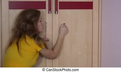 Woman knock closet with hand and find toddler daughter girl...