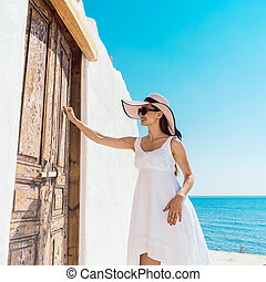 Woman knocking on the door of a beach home in Greece