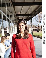 woman, lächelt, mit, studenten, in, hintergrund, auf, campus
