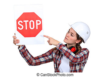 Woman laborer pointing stop sign