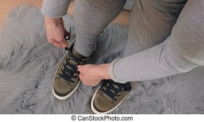 Woman lace up green trainers