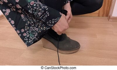 Woman lace up wedge boots on floor