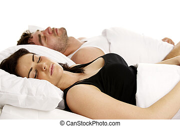 Woman laid in white bed next to a man sleeping