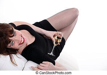 Woman laid with glass of champagne