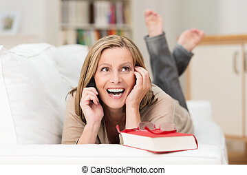 Woman laughing as she chats on her mobile - Attractive...